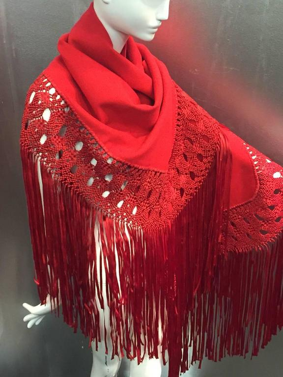 """A stunning 1970s cardinal red wool crepe and macrame ribbon fringed shawl.  Trimmed in beautiful macrame fringe on three sides.   Wool crepe part measures 56"""" x 19"""" plus 24"""" of macrame added to three sides."""
