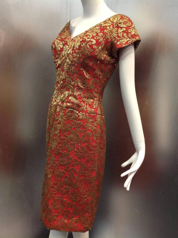 A beautiful 1950s-early 1960s deep red sheath dress with plunging décolletage, gold lame leaf-patterned overlay and scattered garnet-tone stones across the bodice.  Cap sleeves and back zippers.