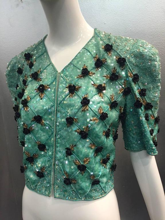 A gorgeous 1980s Carolina Herrera sea foam aqua blue/green intricately bead and sequin encrusted bolero jacket with front hook closure and exaggerated shoulder treatment.  Scattered across the piece, in a trellis pattern, are black resin roses and
