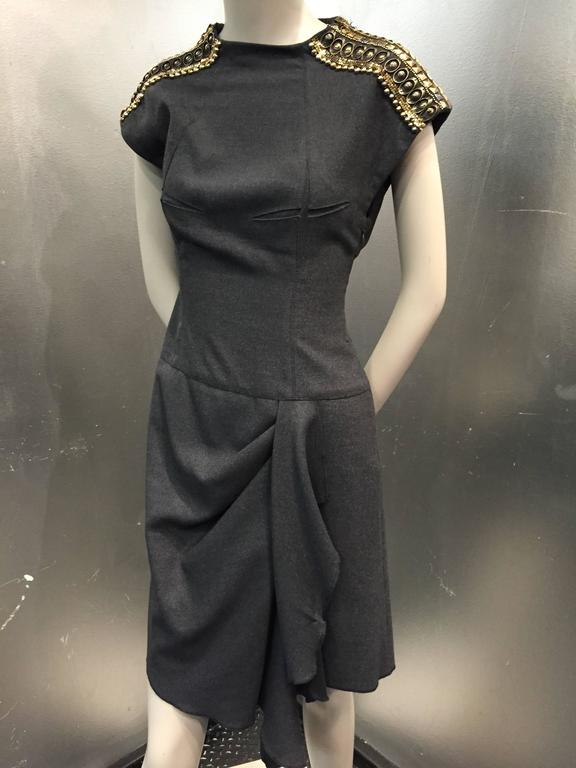 A fabulous Jean Paul Gaultier cocktail dress:  gray flannel, fitted bodice dress with funnel neckline, zip-open shoulders covered in studs and metal.  Front swag, Side zipper and darting interest.