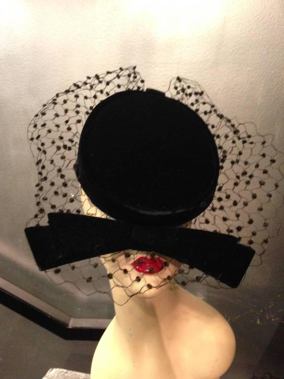 An adorable 1950s Livingston Bros. black velvet cocktail hat with stiff bow and chenille dotted veiling that stands out.  Lined in a pretty floral acetate fabric.