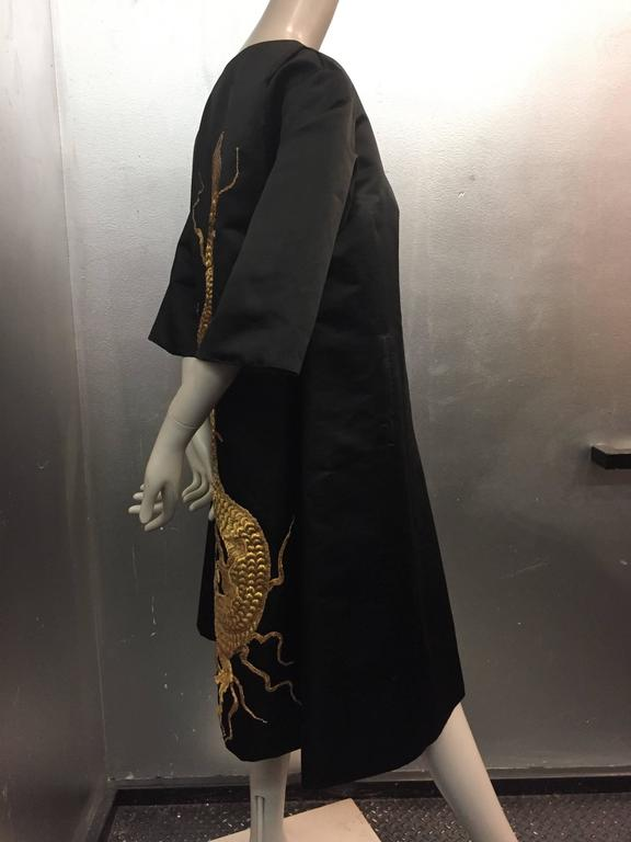 1950s Black silk satin evening coat with stunning antique gold Chinese dragon appliqué.  Lined in tobacco brown silk gazar for structure. Watteau back and 3/4 length sleeves. Side pockets. Dragon appliqué is most likely of a 1920s vintage.