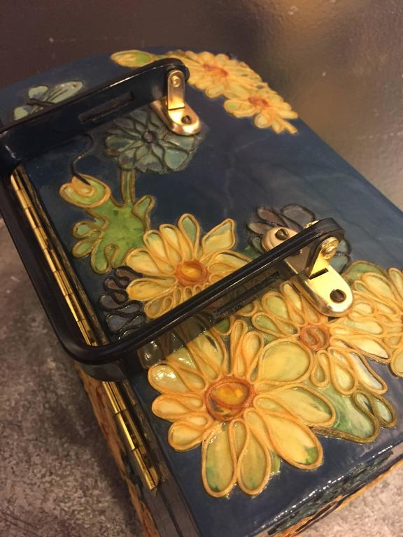 A fun 1960s wooden box purse with lucite handle, painted and applied fabric in a butterfly and floral pattern.  Trimmed with epoxy-ed on embroidery floss.  Interior is velvet lined with more decorative trim and mirror in lid.