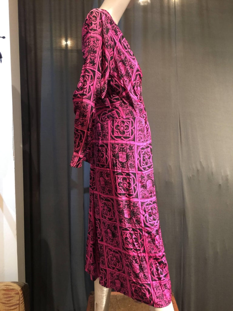 "A stunning 1940s original Adrian design!  A magenta and black ""heraldry"" paneled print crepe dress with sexy right side front slit and diamond shaped inset panel at abdomen, surrounded by gathers in all directions.  Long sleeves and mid-calf length."