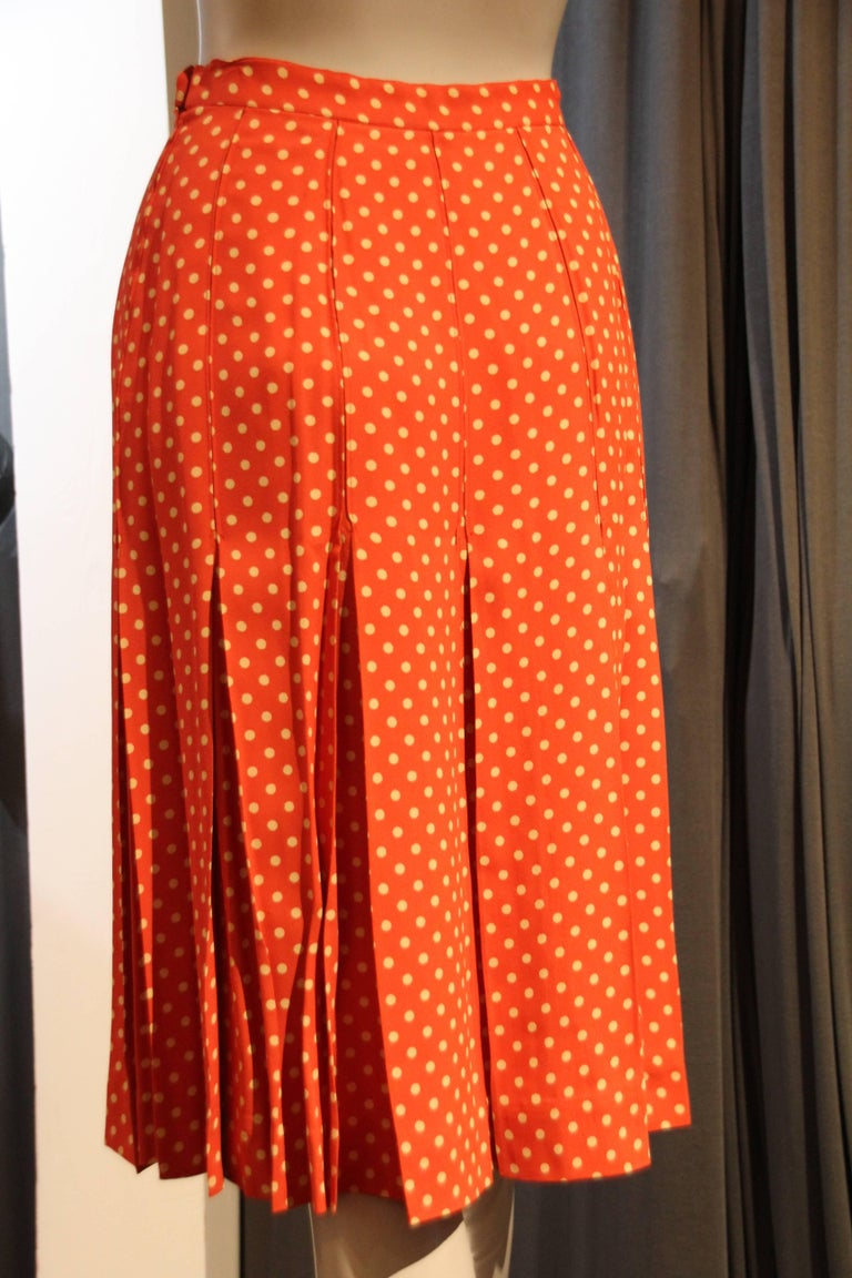 A flirty 1970s Saint Laurent box pleated orange and white polka dot crepe skirt with waistband and zipper.  Just below knee length.
