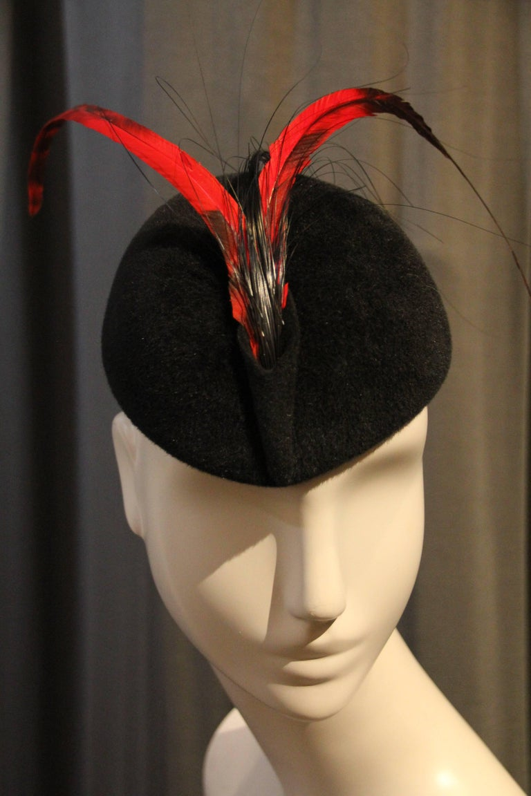 """A charming 1960s Frank Olive black fur felt tilt hat """"beanie"""" style with red and black coque feather trim and a slight point at front edge to be worn at forehead.  Grosgrain ribbon inside band.  Elastic for securing at optimal"""