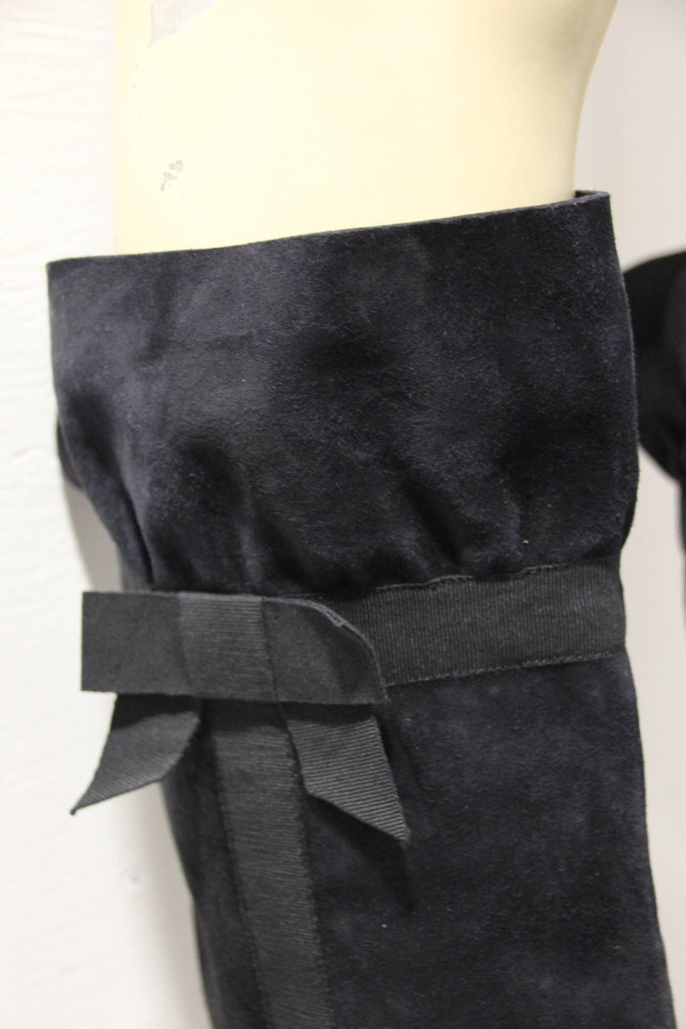 1970's Yves Saint Laurent black suede boots almost up to the curve of the knee. Soft supple black suede make this boot a classic for any Fall wardrobe. Modern black grosgrain ribbon trim at side and nicely tied bow give this boot a feminine touch.