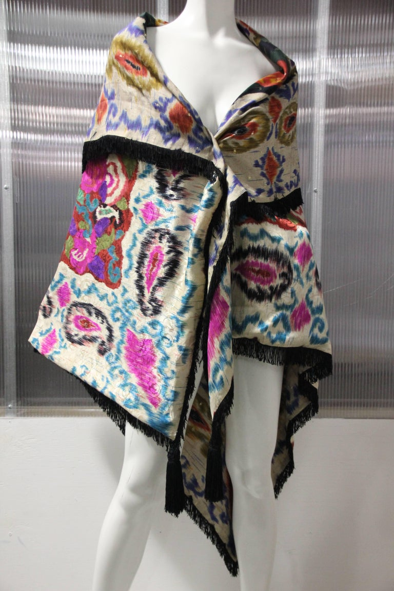 1980's Ungaro of Paris made in Italy silk paisley and floral pattern double-sided large shawl is trimmed in black rayon fringe with large tassels at front points. This stunning and vibrant large silk shawl can be worn in many ways and can be folded