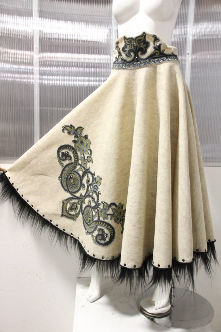 A custom-made ecru wool felt circle skirt in a 50's-style cut with decorative high waistband.  Embellished at waist and skirt with scroll-work applique and grommets.  Hem is trimmed in black wispy fur and grommets. Zippered in back.