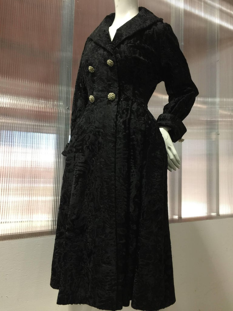 This stunning and rare broadtail fur coat dress by Hattie Carnegie has a dressy and formal nature. The silhoutte is nipped-in at the waist and a pleated back full skirt falling below mid-calf length emphasizes the bust and hips: Quite evident in