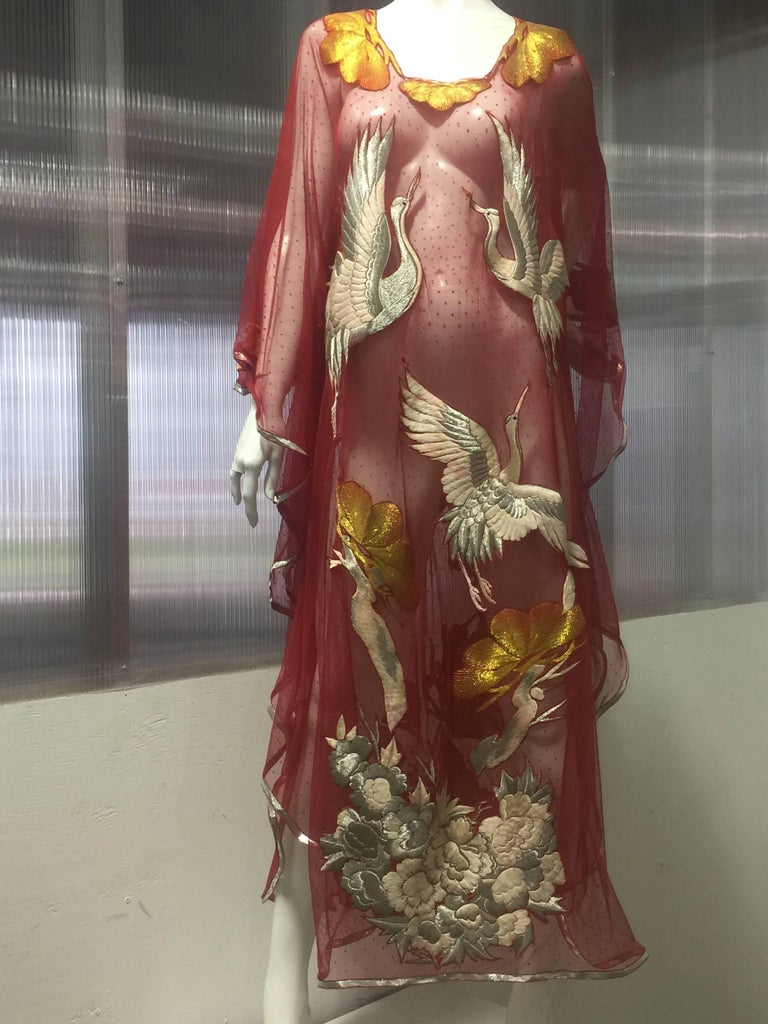 This custom made Torso Creations Kaftan of red pointe d'esprit netting is entirely appliqued with scattered silk floss flowers and silver embroidered Manchurian Japanese Cranes in flight . These rare and graceful Cranes are known as a symbol of