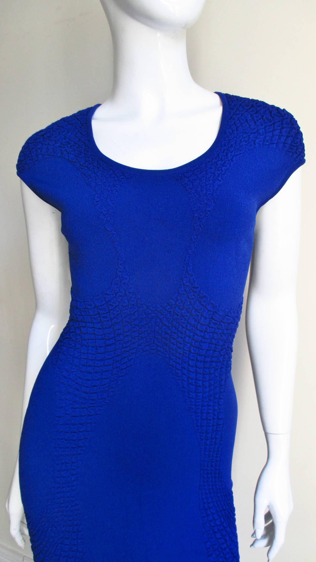 A vibrant blue knit bodycon dress from Alexander McQueen. It is highlighted down the front and back with strategically placed figure enhancing subtle pebble textured knit detail in the same fabric. It has a crew neckline and cap sleeves. There are