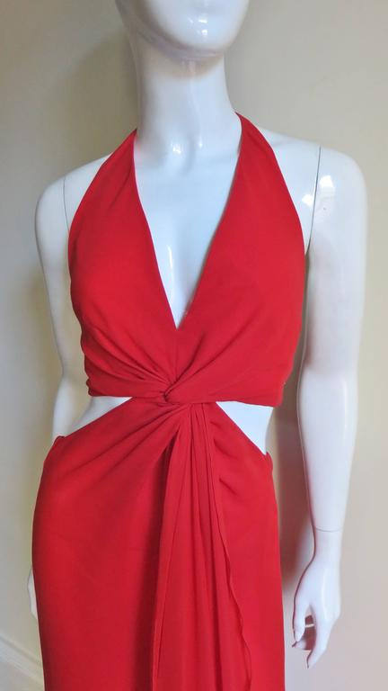 A fabulous red silk gown from Valentino.  It has a plunging halter neckline twisting at the center front with a low cut to the waist back with a cross strap at mid back.  The sides are open above and below the waist.  There is a center front skirt
