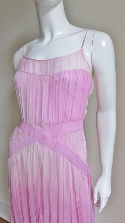 A gorgeous John Galliano silk ombre gown in shades of pink.  Spaghetti straps emanate from a small sheer band around the top of the bodice.  From here a layer of silk gathers onto 2 angled crossing bands at the waistline then continues forming an