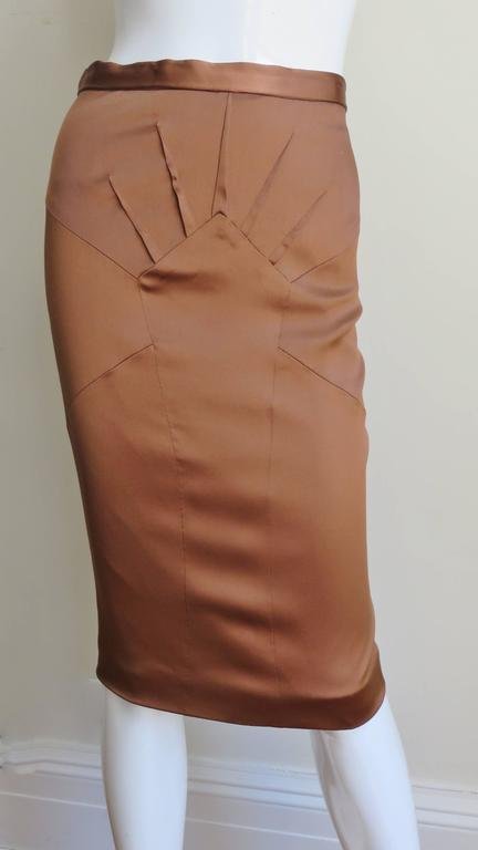 A beautiful bronze stretch silk pencil skirt from Dolce & Gabbana. It has a waist band plus fabulous seaming and darts radiating from a center front panel.   It is lined in same fabric and has a center back zipper. New with tags.  Fits sizes Small,