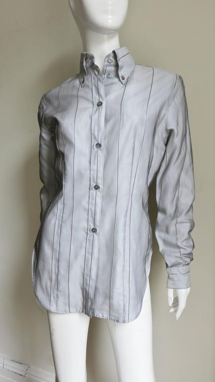 A fabulous 2 piece silk set by Alexander McQueen.  It is made of grey sheer silk with fine black and silver stripes over white cotton.  The shirt has a high button down collar, button front, long sleeves with button cuffs, a back yoke and shirt tail