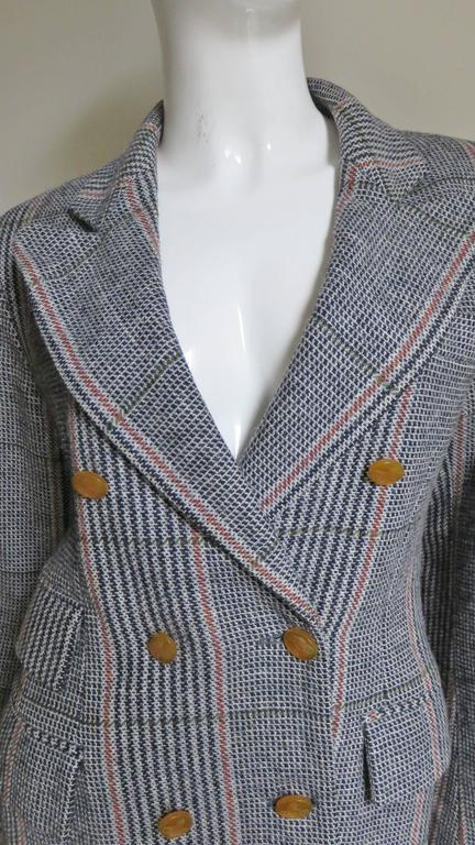 A great black, grey and toffee wool plaid jacket by Vivienne Westwood from her red label collection.  It is double breasted with signature etched toffee colored buttons along the front and on each cuff.  It has peaked lapels and slight shoulder