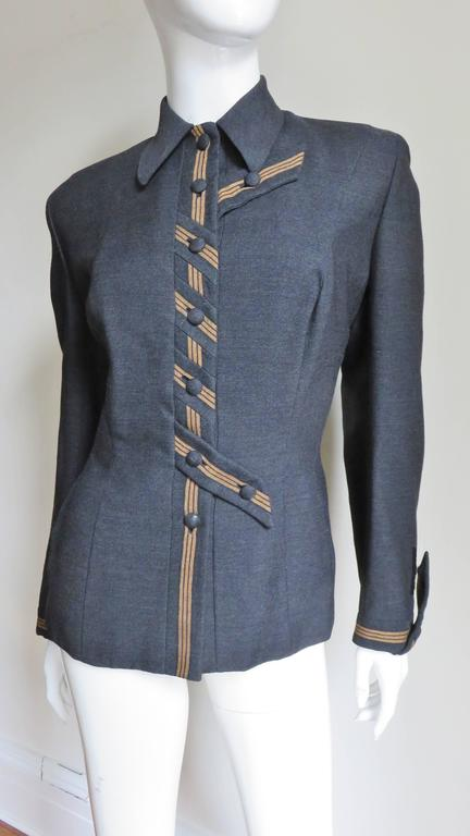 A stunning 1940's charcoal wool jacket by Milgrim.  It has a shirt collar, princess seaming and shoulder padding.  The front closes with self covered buttons on a placket with toffee colored striping.  The center 3 buttons are placed angled on the