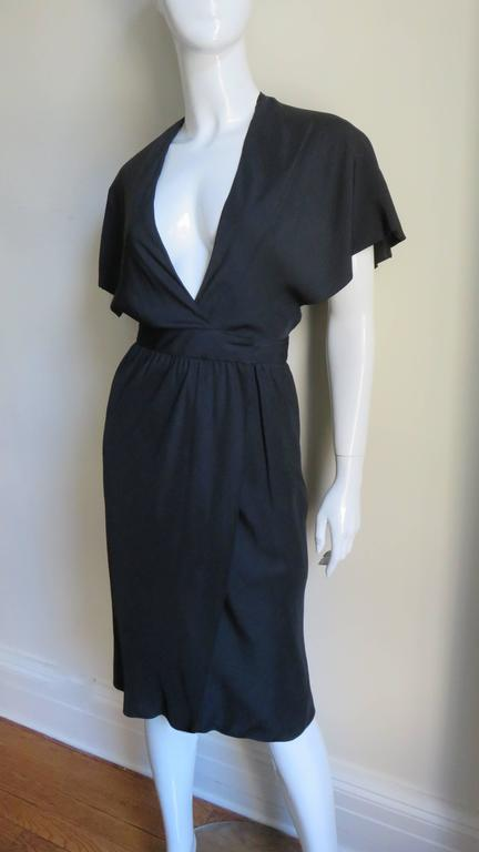 A beautiful black silk dress from Halston. It has a plunging neckline, cape sleeves and wraps at the front waist. The skirt portion is straight and gathers onto a waistband which closes at the side waist with a metal hook. It is fully lined in black