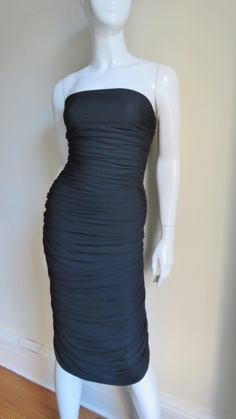 A pretty black slinky knit dress from Vicky Tiel.  It is strapless and horizontally ruched from top to bottom front and back.  The bodice has side boning, a side zipper and black lining.   Fits sizes S, M.  Bust  34-36