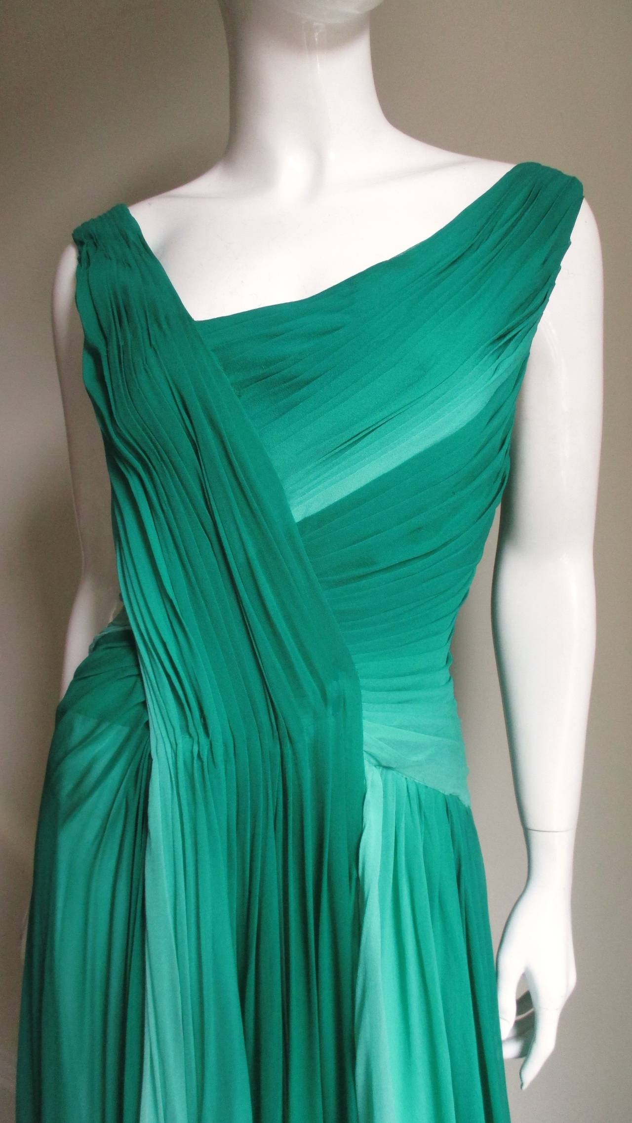 A fabulous gown from Monique Lhuillier in emerald green to off white ombre silk.  It has an asymmetric neckline crossing the front and back at different angles of pleating, one side going the length of the center front and forming a long shoulder
