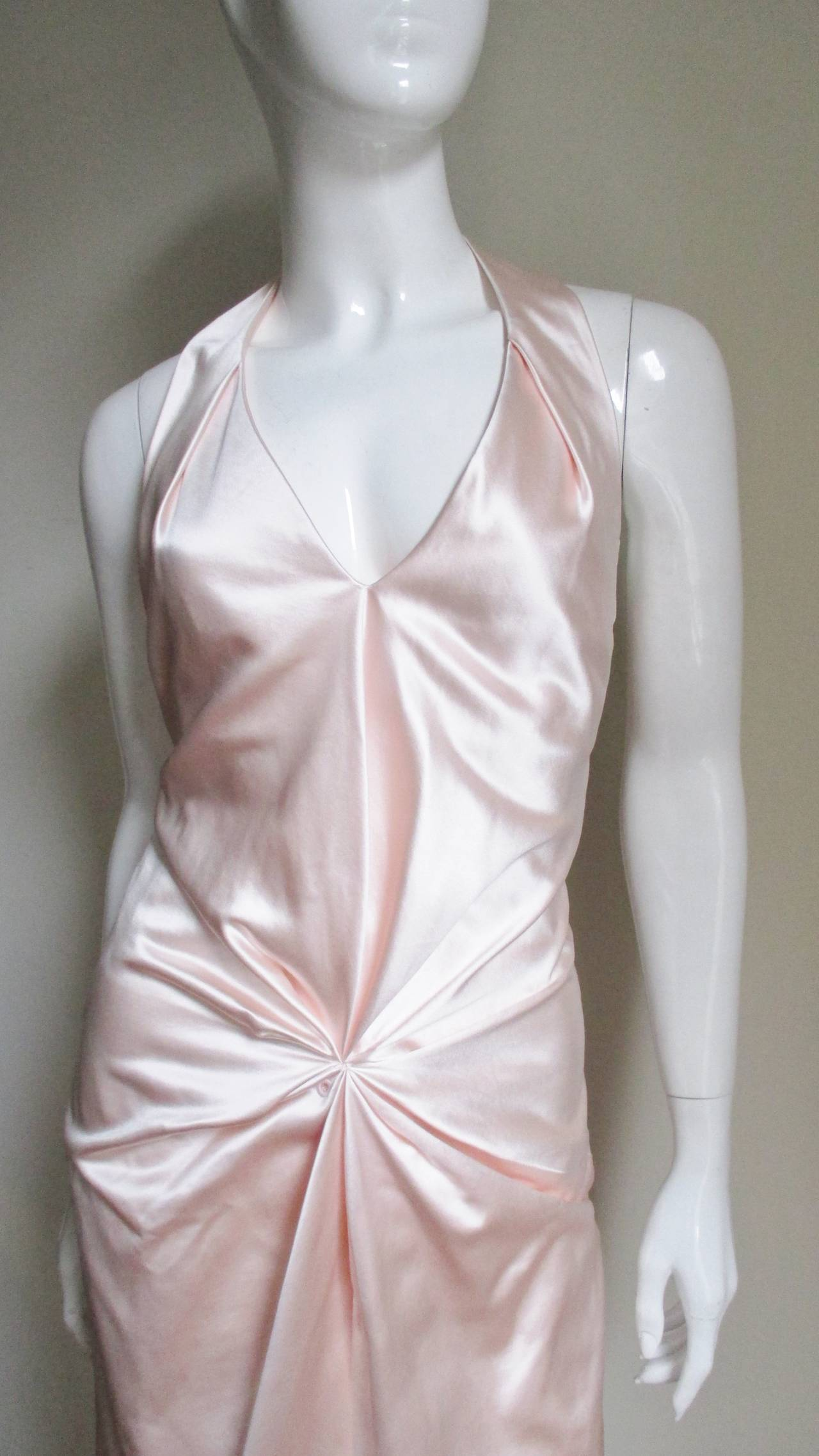 A silk peau de soie dress in a delicate shell pink.  It has a plunging halter neckline and gathering to the center front lower abdomen.  The dress is fully lined in matching light weight silk, has a matching side invisible  zipper and clear snaps at