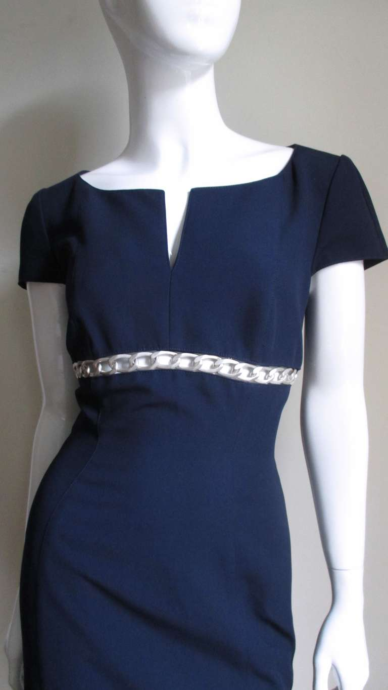"A fabulous simple navy blue dress from Thierry Mugler in a synthetic blend.  It has a scoop neckline with a slit, top seamed cap sleeves and an inset just under the bust line with a strip of 1"" hammered large link silver chain.  The dress is"
