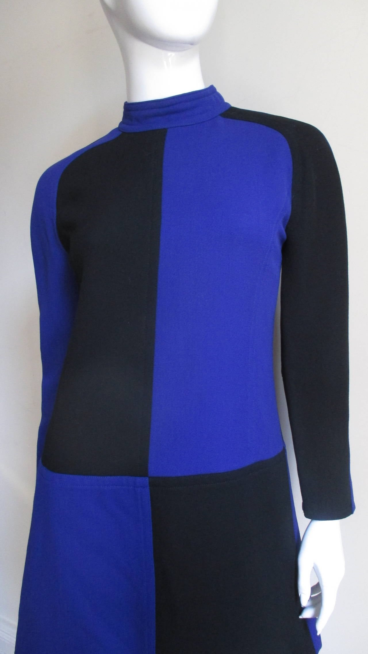 Beautiful color block wool mini dress with alternating black and royal blue by Courreges.  Stand up collar, back zipper, raglan sleeves and fully lined.    Excellent Condition. Fits Small, Medium.  Measurements Bust  34
