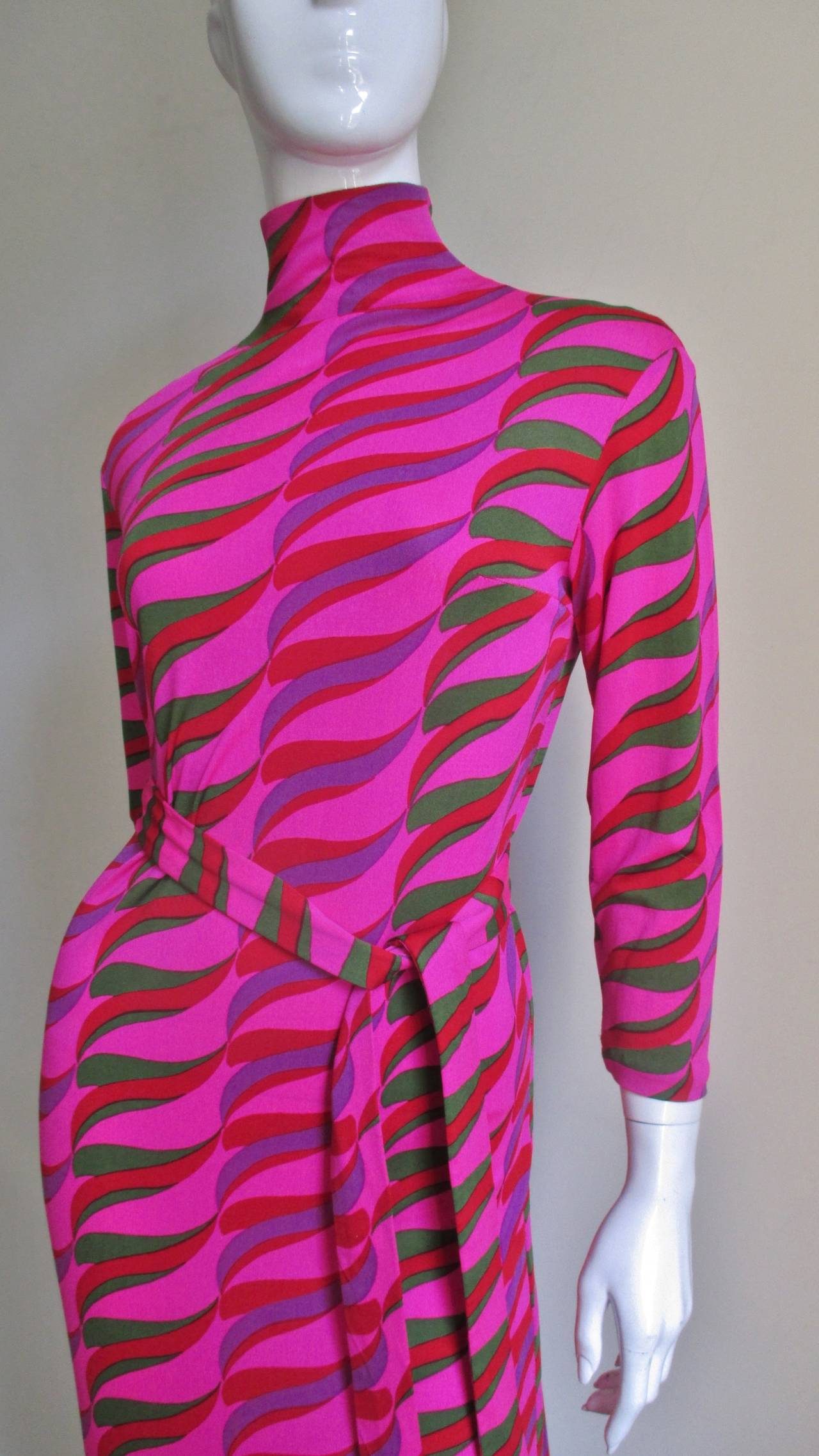 A vibrant pink silk knit long belted dress from La Mendola.  Simple full length sheath with a stand up collar in an abstract pattern of green, purple, red on a bright pink background.  The back closes with a length of self covered buttons and silk
