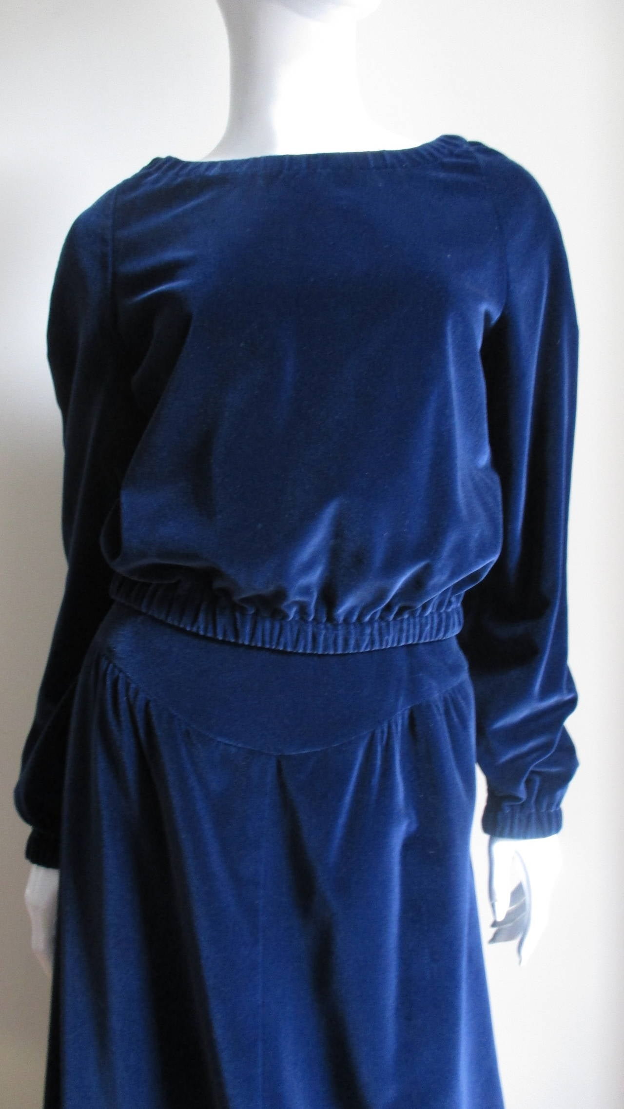 Two piece velvet set from Courreges in between sapphire and navy blue  in color.  Maxi skirt is gathered into a curved yoke front and back. The bateau neck blouson style top has elastic at raglan sleeve wrists, waist and neck. The top slips on over