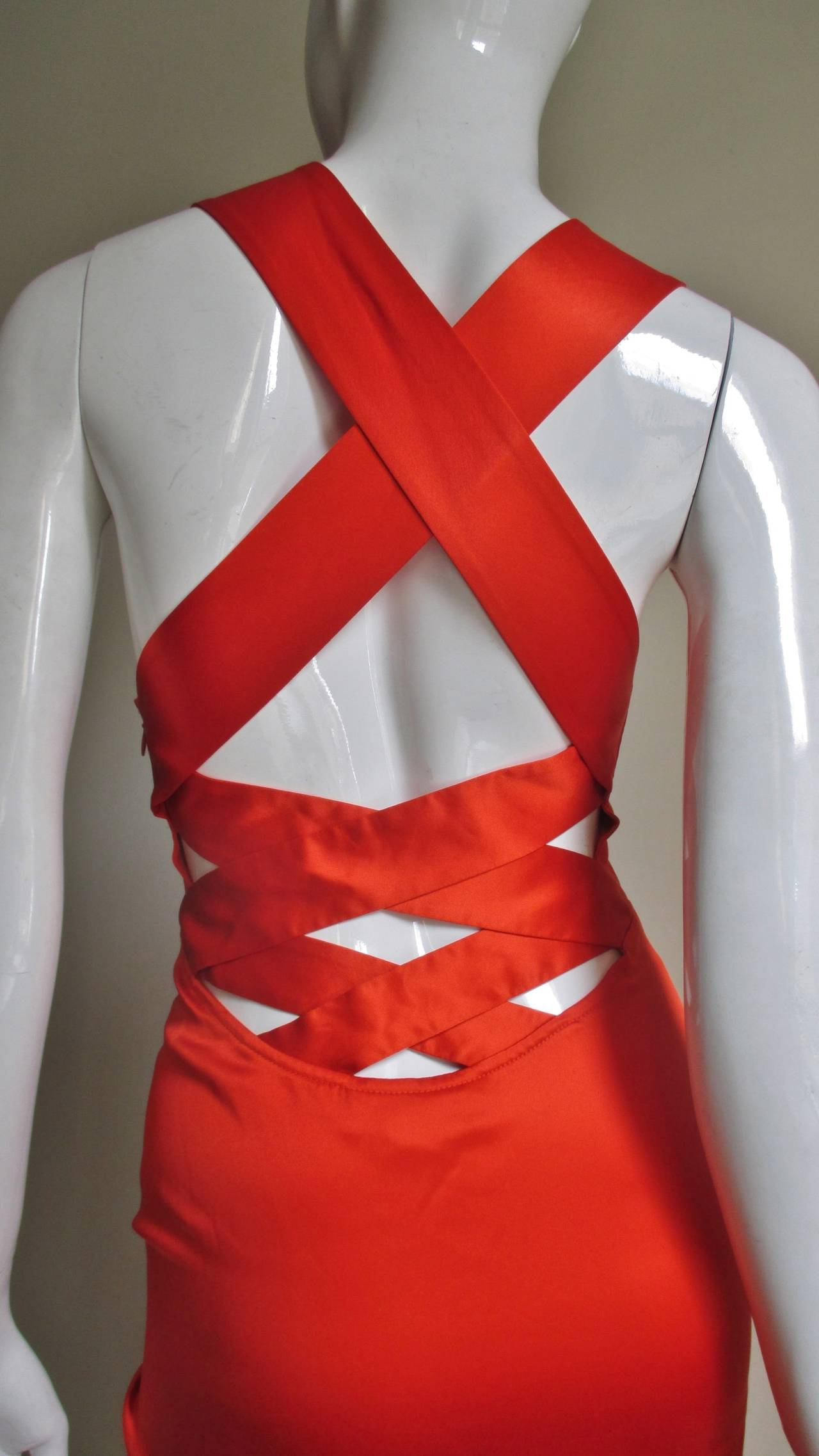 A vibrant orange fine silk dress from Versace.  It has a low cut gathered front which is attached to a fitted bodice.  The fitted skirt portion is pieced in angles front and back.  The back is absolutely stunning, low cut with larger  straps