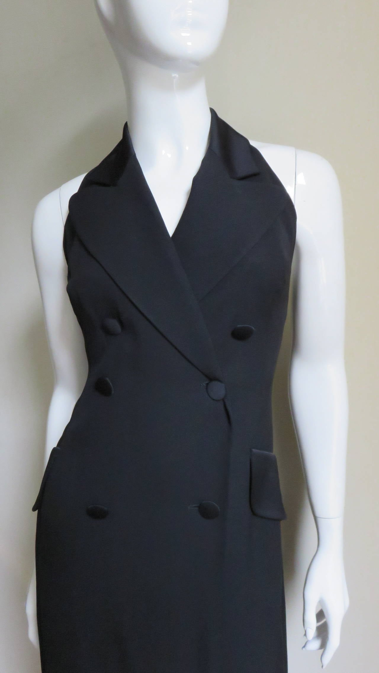 A fabulous black halter tuxedo jumpsuit in crepe back satin.  It is a double breasted jacket style bodice with 6 buttons matching the satin peak lapels and pocket flaps.  It is fitted through the waist with princess seaming.  The lower portion