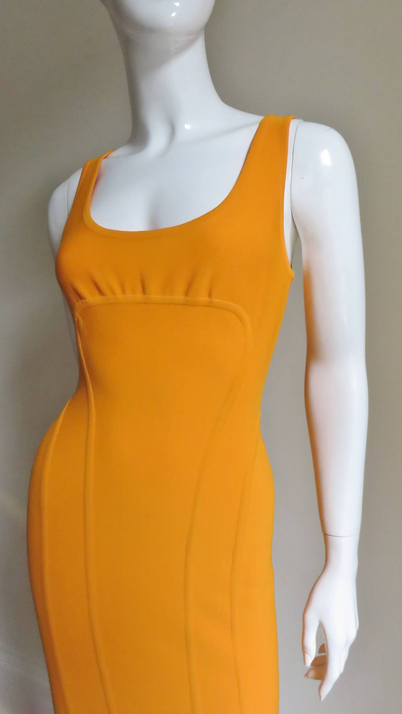 A great dress from the master Herve Leger in a fabulous marigold color stretch bandage fabric.  Typical form and fit he is known for including multiple seaming which enhance shape.  It is sleeveless with a scoop neckline and curved seaming under the