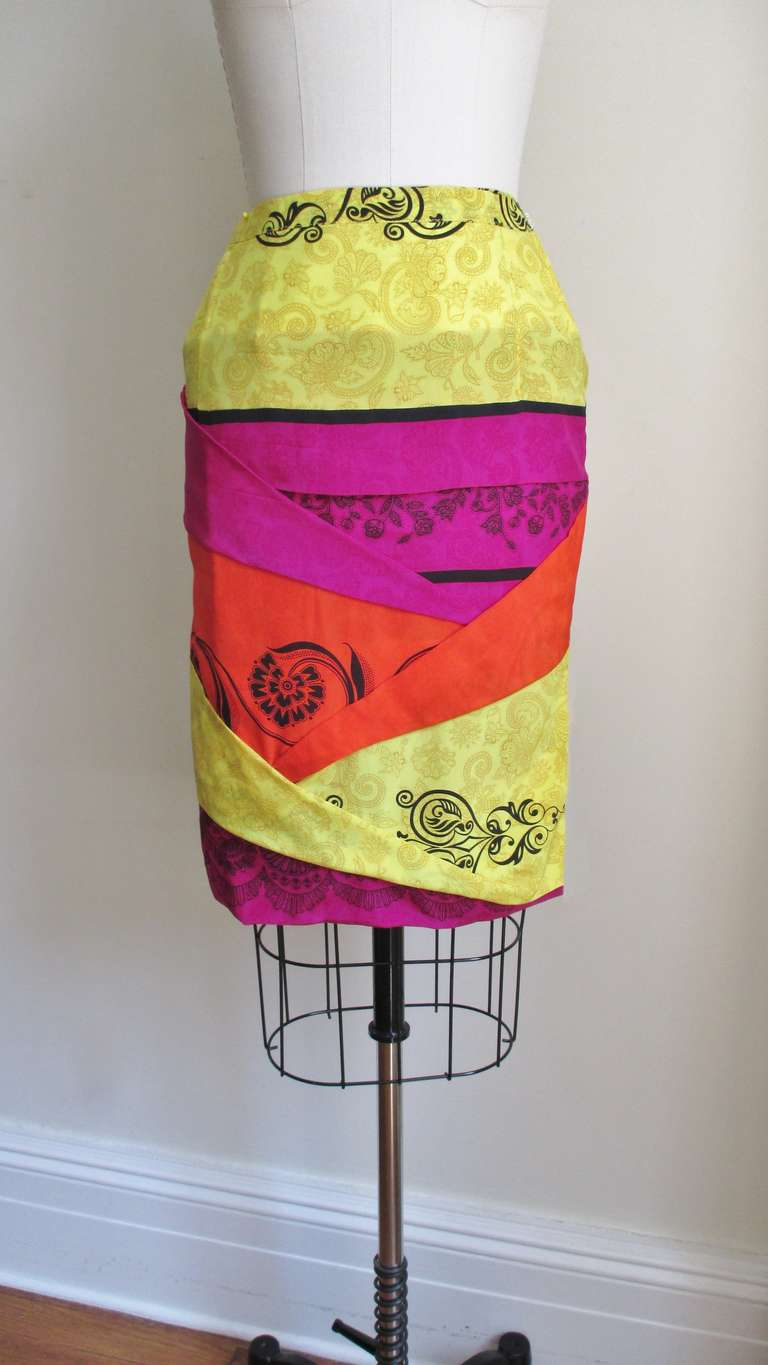 A fabulous silk skirt from Gianni Versace in yellow, orange and magenta silk accented with a black screen print of abstract shapes and flowers on top.  It has a number of angled pleats or folds accentuating the fitted wiggle shape of the skirt. It