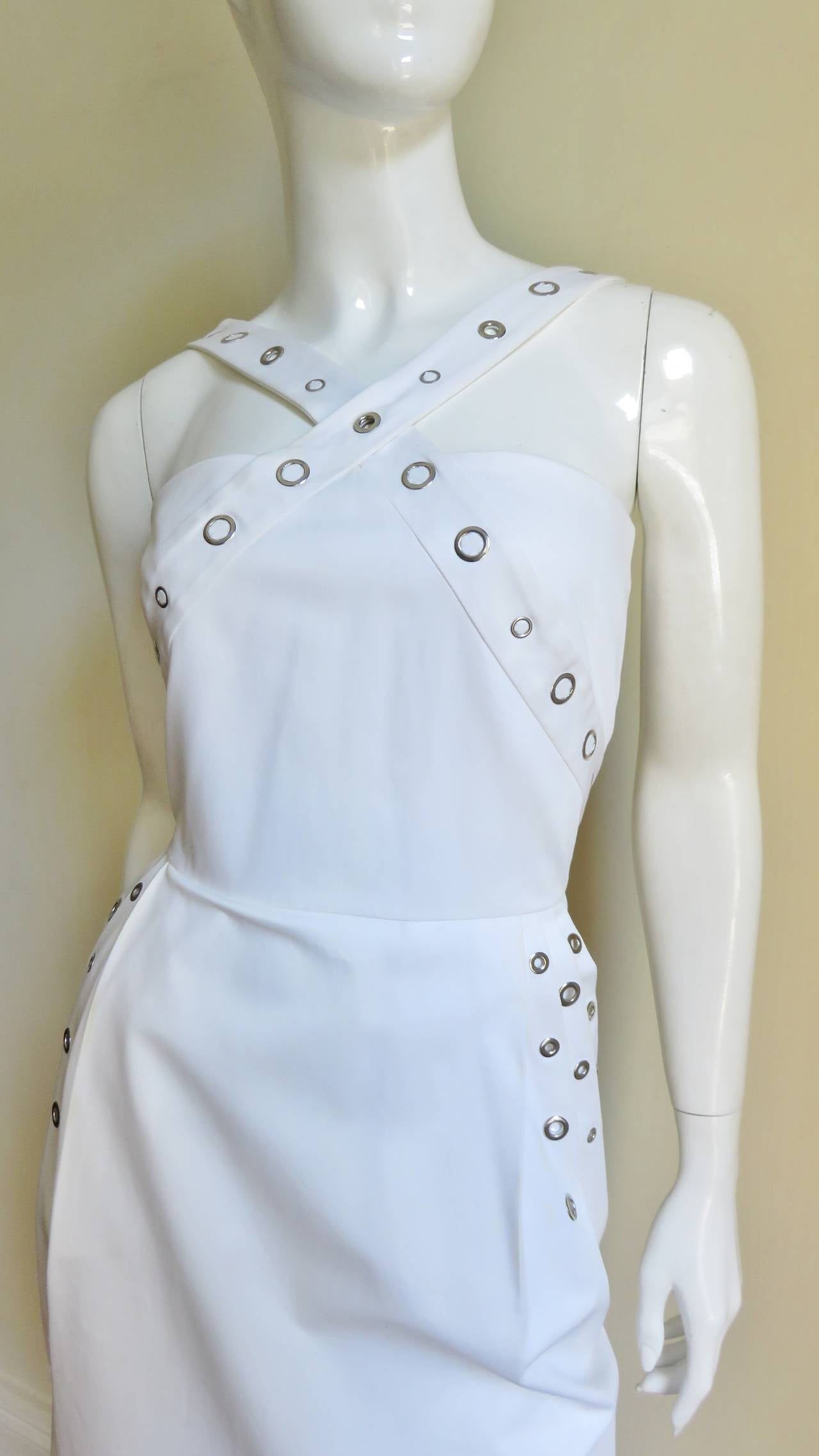 A great white dress from Jean Paul Gaultier in a cotton twill with a little stretch. The fitted bodice has straps crossing front and back. The skirt is semi fitted with 4 pleats at the at the waist the last of which forms hip pockets.  That extra