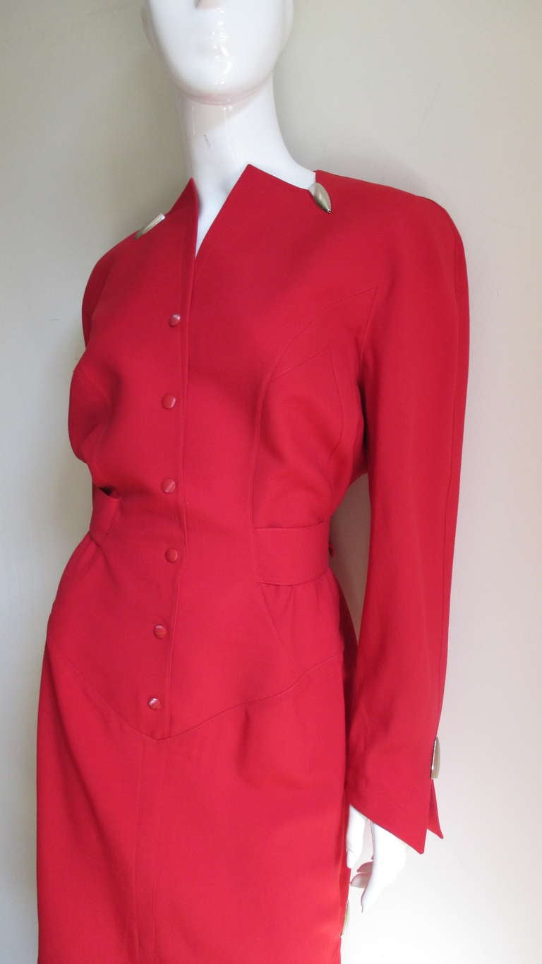 A great red light weight wool blend dress from Thierry Mugler.  The dress is fitted at the back with a half belt with a matching buckle and is highlighted at the small side slit, split cuffs and collar with silver bullet shaped hardware.  It has