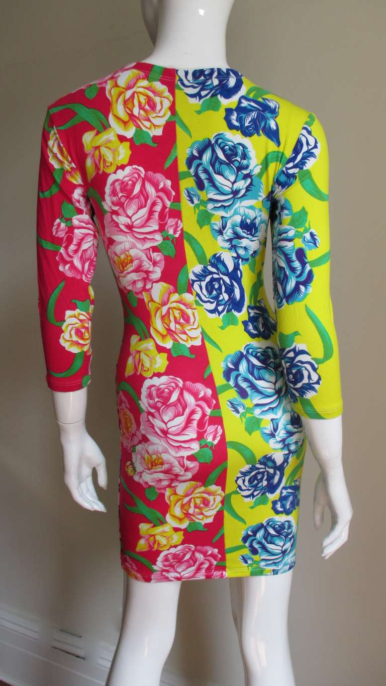 A fabulous brightly colored mini dress in a silk cotton knit from Gianni Versace's Versus line. A simple body conscious dress that slips on over the head in 3 different brilliantly colored and intricate flower patterns 1 front and 2 back.  It has