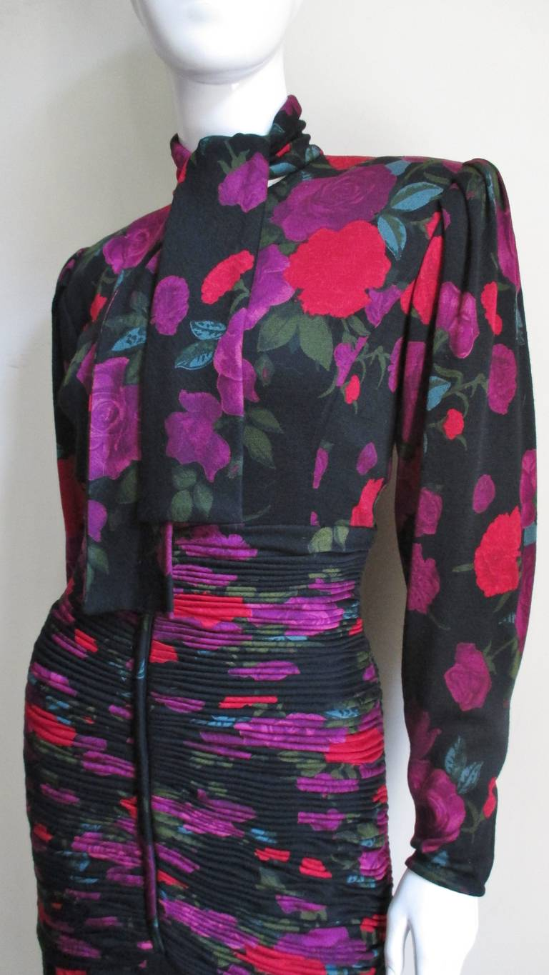 A very pretty wool jersey body conscious dress from Emanuel Ungaro. The purple and red flowers pop against the black background. It has a tie neckline, full sleeves with zipper cuffs and fabulous, beautifully intricate ruching around the dress from