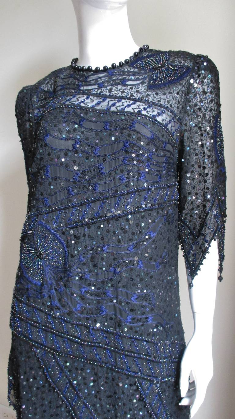 A gorgeous beaded, sequin embroidered dress from Zandra Rhodes.  Made of semi sheer black silk embellished throughout with embroidery, sequins and beads which shine in shades of blue and purple.  There are randomly placed inticatly beaded