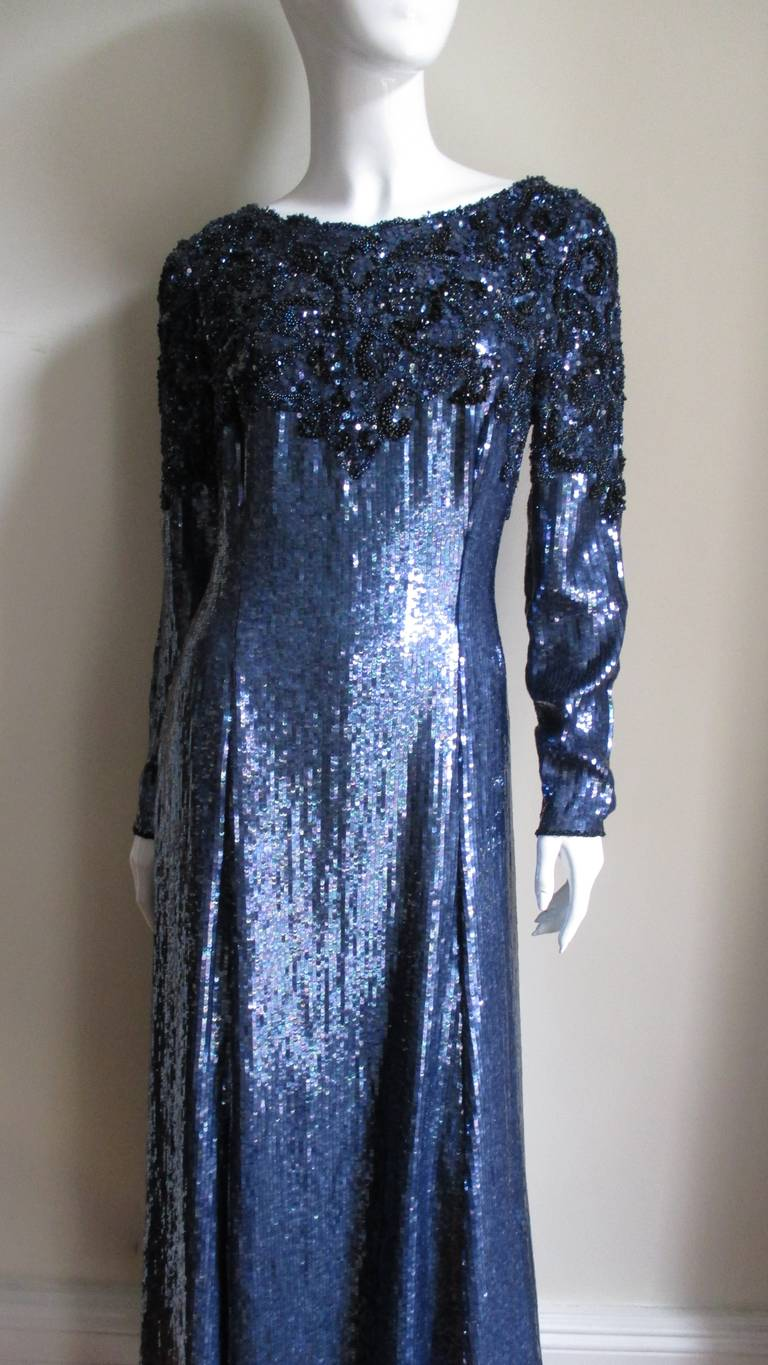 This is a gorgeous deep sapphire blue sequin and beaded gown by Louis Feraud.  It  has a softly rounded neckline in the front with deep V in the back.  The chest, upper arms and back V are covered in an elaborate pattern of blue glass seed beads and
