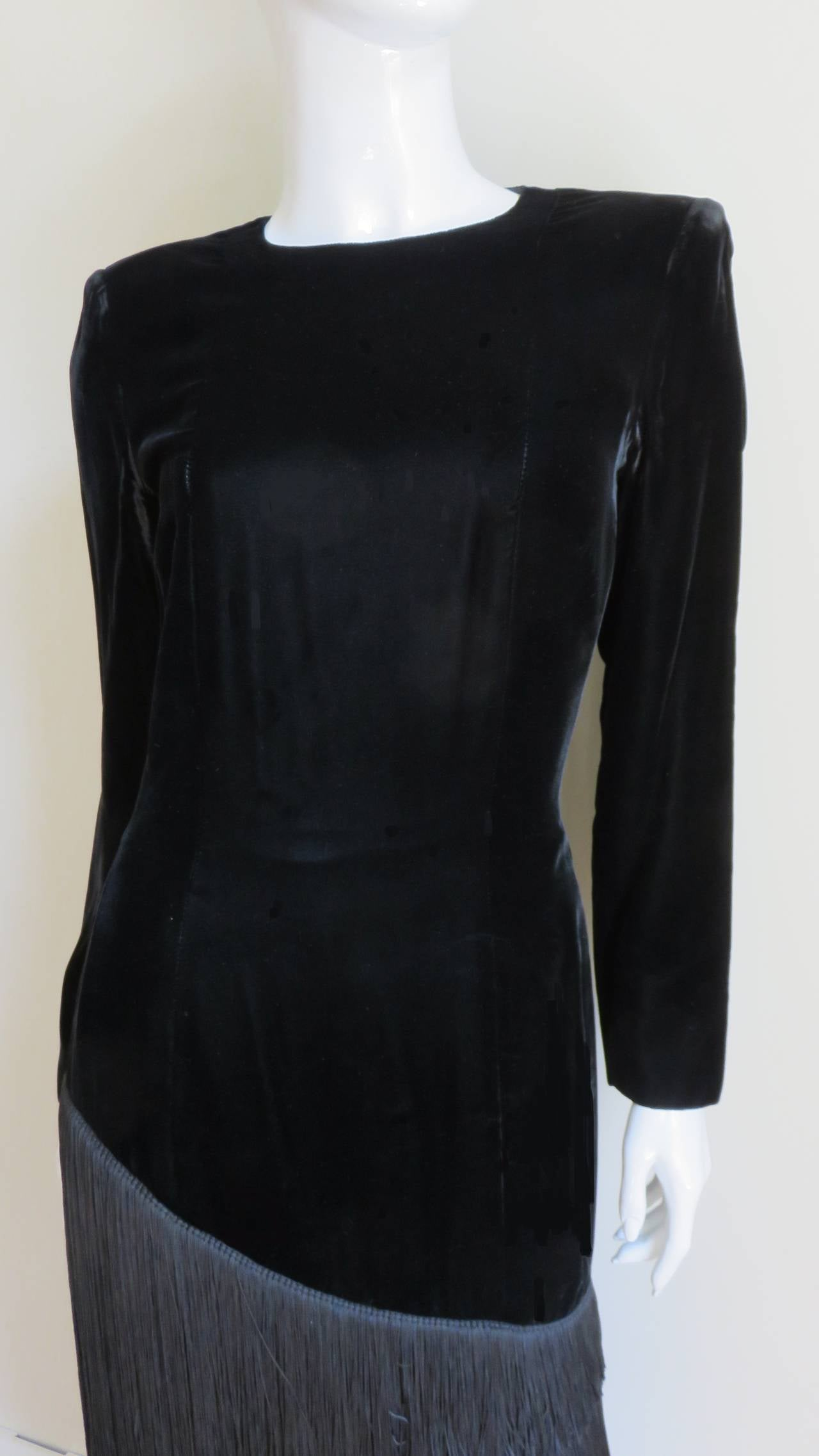 "A black velvet vintage dress from Lanvin. It is a simple long sleeved sheath with a crew neckline.  It is fitted through the waist and the falls straight to hem. A curved row of silk fringe gradated from 11-3"" in length falls diagonally from"