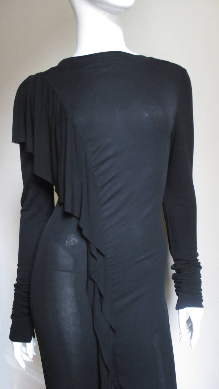 A super black silk jersey dress from Jean Paul Gaultier.  It has a bateau neckline and fitted with a gradated ruffle starting at the front of one shoulder straight down the front to an opening above the knee.  The sleeves are extra long meant for