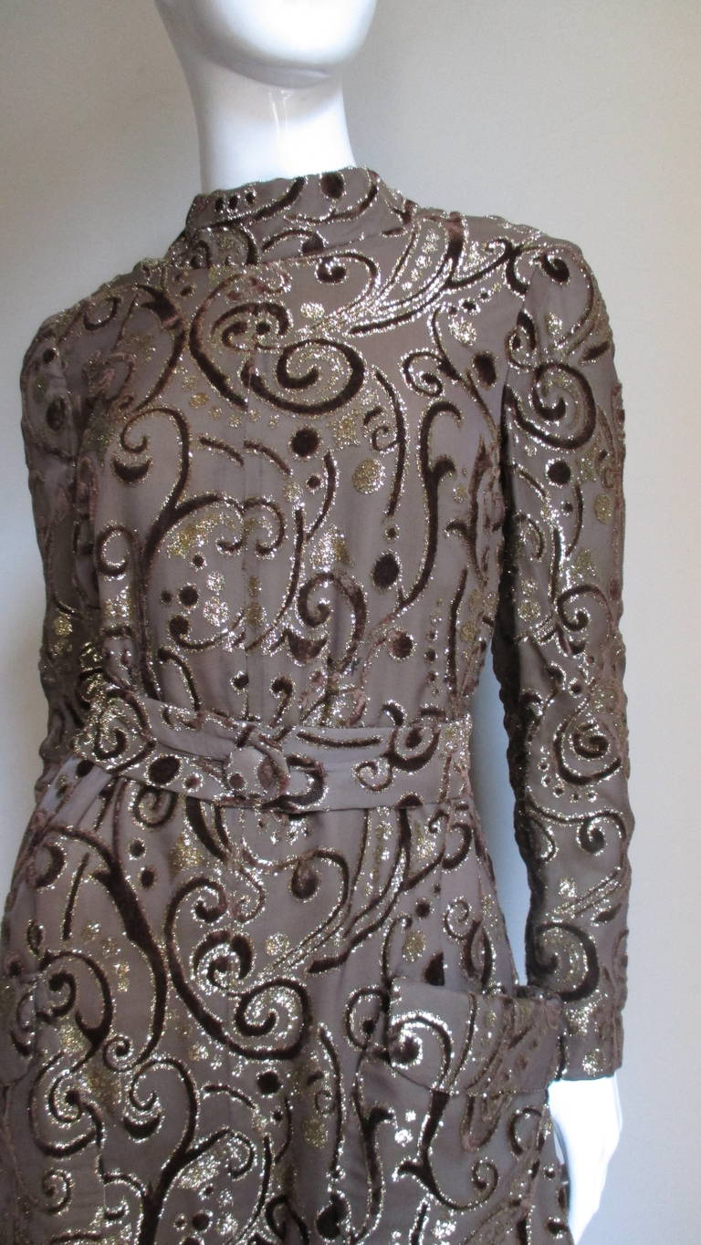 A tent dress with matching belt in taupe silk background with scrolls and circles in gold lurex and brown cut velvet from Master designer Pauline Trigere.   The dress flares from underarm to the hem and looks attractive with or without it's matching