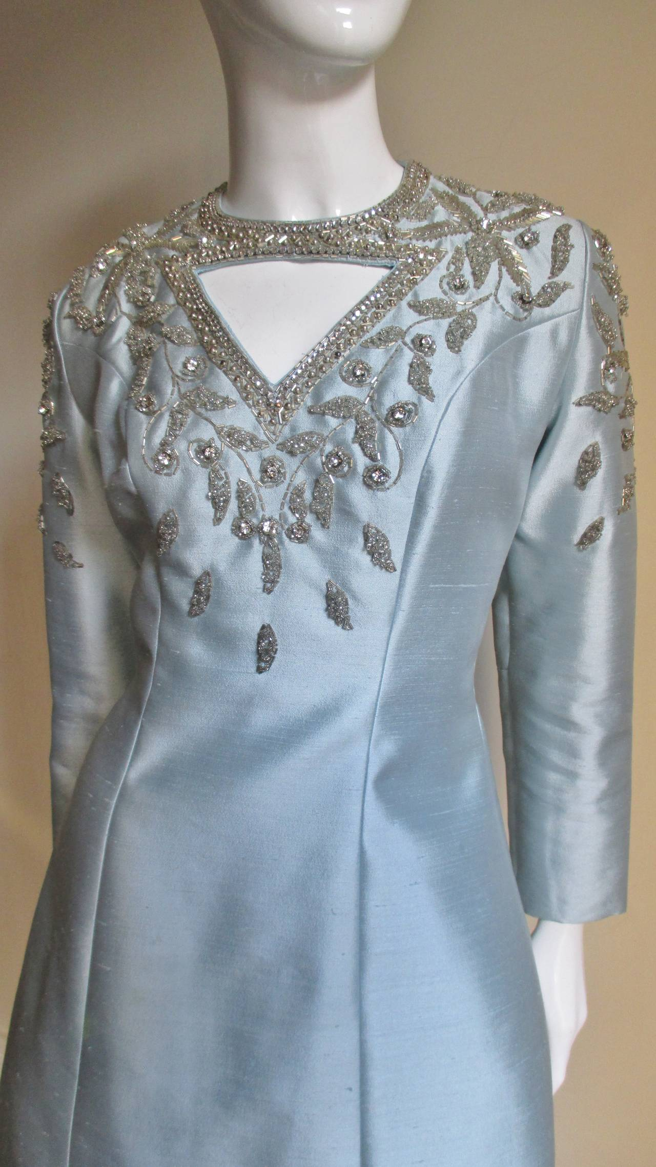 Beautiful baby blue silk beaded and rhinestones dress from Bernetti, New York.  Princess seamed for shaping with triangular cutouts just below the neck front and back.  Both are outlined in prong set rhinestones and elaborately framed in silver