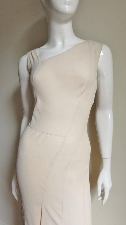 A Christian Dior gown in a pale shade of blush silk, reminiscent of the 1930's.  A long fitted sleeveless silhouette with asymmetrical neckline and seaming.  Seaming starts at one shoulder angling down to the center front thighs.  There is a waist