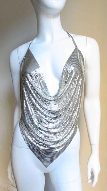 A great silver metal mesh halter top. The neckline drapes with the amount of exposed decolletage controlled by leather ties at the neck.  The center front hem comes to a point and there are also ties at back waist level leaving the back almost