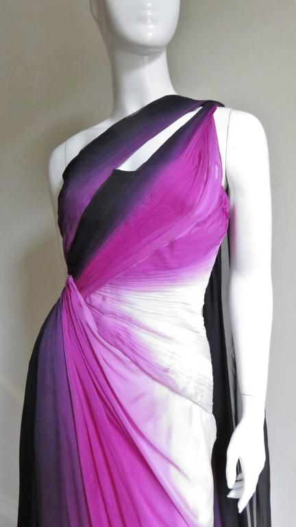 A gorgeous dress from Monique Lhuillier in shades of purple, pinks and white silk.  Tiny pleating angles from the one shoulder across the front and back to the side waist.  There is also a slit for a flash of flesh on the same angle front and back.