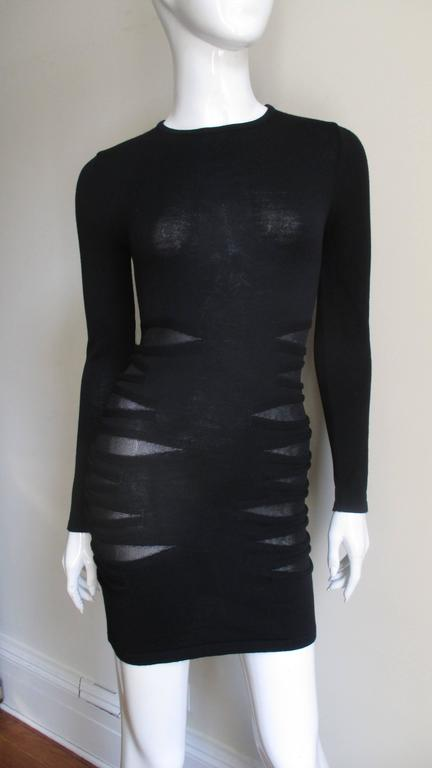 Versace finely knit wool body hugging dress with sheer covered cut-outs at side waist and hips.  Cut-outs are accentuated by the edges being bound in same fabric. Slips on over the head.  Stunning.   VINTAGE SCHIECK Excellent condition.  Bust