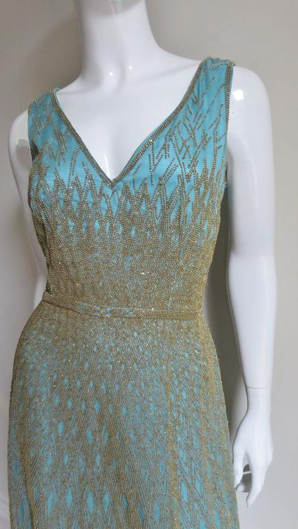 So gorgeous.. an aqua silk gown covered in an intricate design of gold glass beading by Carolina Herrera.  It has a V neckline, fitted waist and full skirt.  All are covered with a detailed pattern of gold beading on sheer aqua silk organza