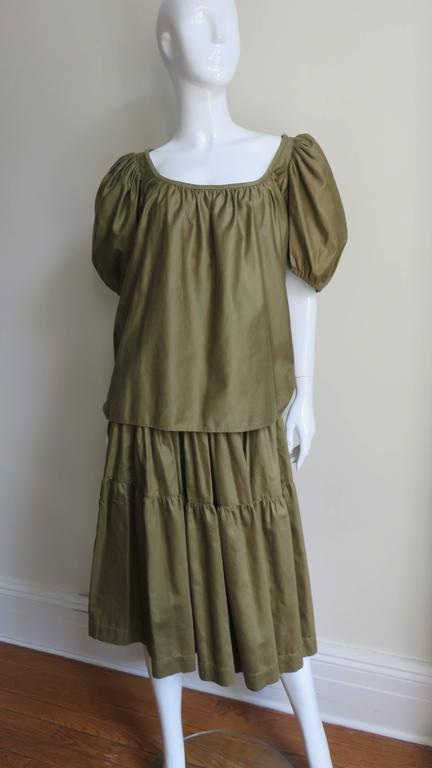 A fabulous 1960's top and skirt from YSL Rive Gauche in olive polished cotton.  The blouse is peasant style with gathered puff sleeves and a wide  gathered square neckline.  The skirt has a fitted waistband, 3 gathered panels each widening towards